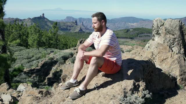 man sitting on rock staring into the distance