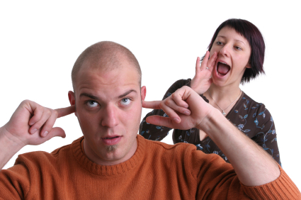 Woman shouting at man with his fingers in his ears